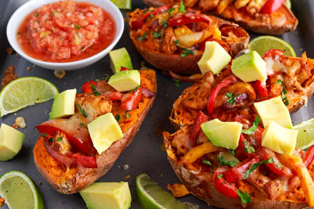 hot baked sweet potato stuffed with yellow, red pepper, chicken, cheese, herbs and salsa. selected focus.