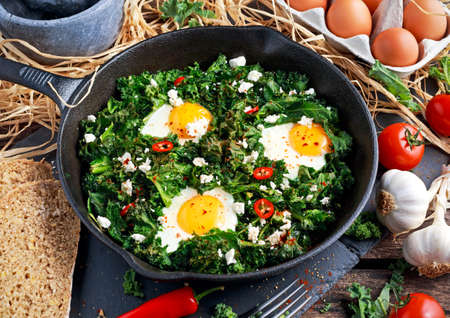 Homemade Green Kale with eggs, feta cheese, herbs, chili in iron pan. healthy rustic breakfast.