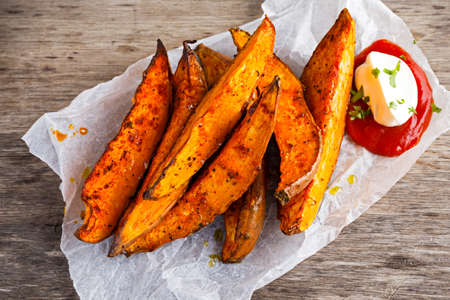 potatoe: Sweet potato fries in paper wrap executed in metal serving basket with fresh cream dip souce on old wooden table. Stock Photo