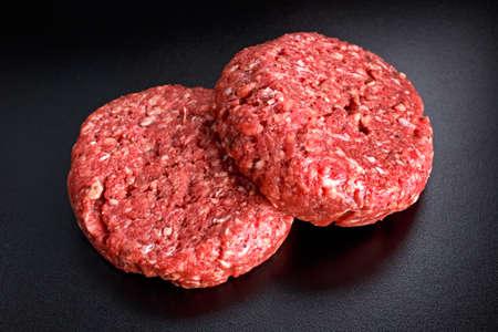 Home HandMade Raw Minced Beef steak burgers on black board. Stock Photo