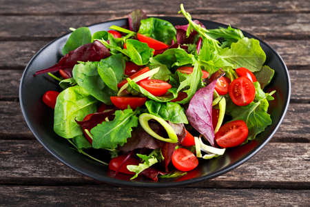 Baby leaves salad with cherry tomatoes and leek rings.