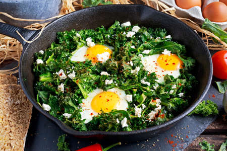 poach: Homemade Green Kale with eggs, feta cheese, herbs in iron pan. healthy rustic breakfast. Stock Photo