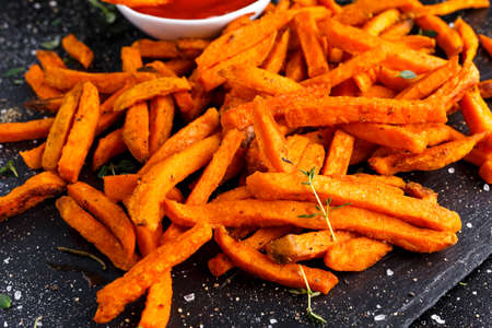Healthy Homemade Baked Orange Sweet Potato Fries with Ketchup, herbs, salt and pepper Foto de archivo