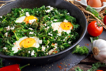 Homemade Green Kale with eggs, feta cheese, herbs in iron pan. healthy rustic breakfast. Stock Photo