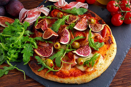 pimiento: Fig pizza with bacon, green pimiento olives, rocket and basil leaves.