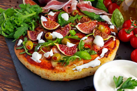 Fig pizza with bacon, green pimiento olives, rocket and basil leaves.