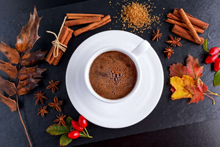anis: Black hot coffee in white cup with anis stars, brown sugar and cinnamon sticks on stone board autumn theme. Stock Photo