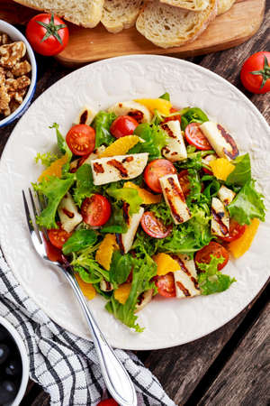 haloumi: Grilled Halloumi Cheese salad witch orange, tomatoes and lettuce. healthy food.