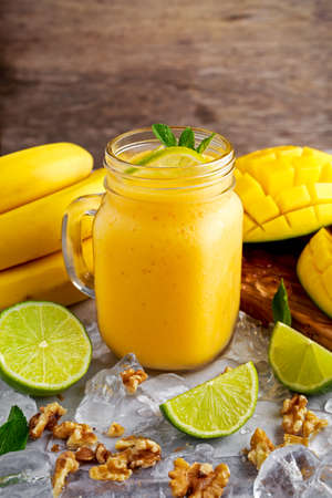 Healthy ripe Yellow Banana Mango Smoothie with slices of Lime, mint and ice. Фото со стока