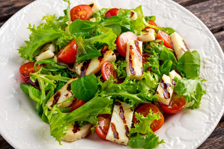 haloumi: Grilled Halloumi Cheese salad witch tomatoes and lettuce. healthy food. Stock Photo