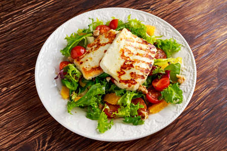 Grilled Halloumi Cheese salad witch orange, tomatoes and lettuce. healthy food. Imagens - 64552704