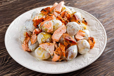 Salmon and young potato warm salad with a lemony yogurt dressing. Stock Photo