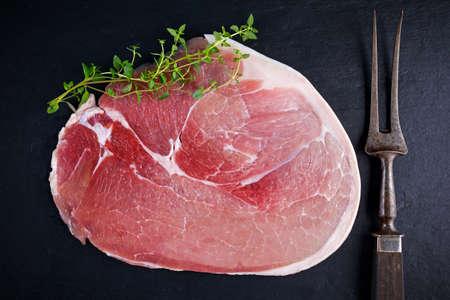 Raw gammon steak on black stone background.
