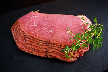 Peppered roast beef pastrami slices on black stone background with herbs.