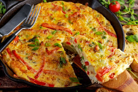 Frittata made of eggs, potato, bacon, paprika, parsley, green peas, onion in iron pan. on wooden table Archivio Fotografico