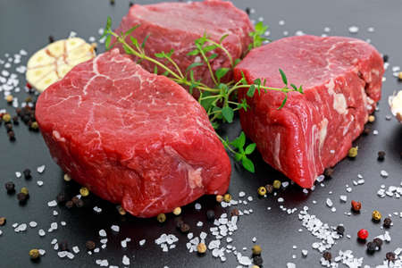 Fresh Raw Beef steak Mignon, with salt, peppercorns, thyme, garlic Ready to cook.