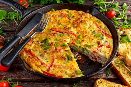 나무 테이블에 철 냄비에 계란, 감자, 베이컨, 파프리카, 파슬리, 녹색 완두콩, 양파, 치즈로 만든 프리 타타