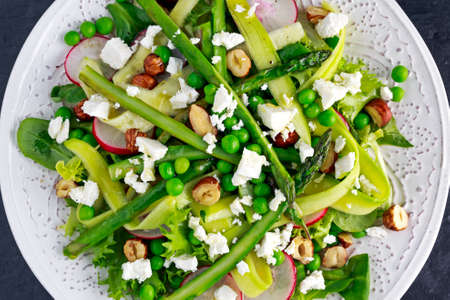 fruit plate: Fresh Green Asparagus salad witch Goat Cheese, peas, radishe, zucchini, lettuce and Hazelnuts Stock Photo
