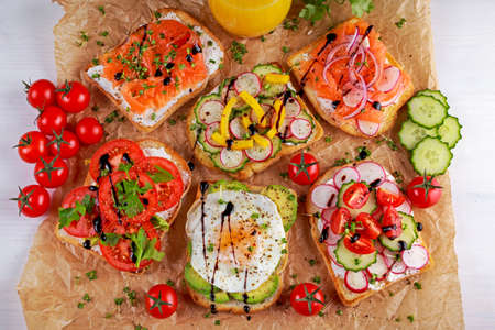 Variety of vegetarian toast sandwiches with salmon, raddish, tomatoes, cucumber, avocado,fried egg and sweet pepper.