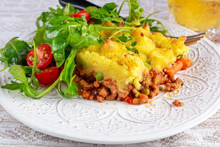baked meat: Traditional british shepard pie on plate with salad.