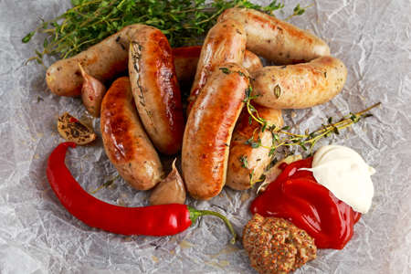 Home-made Pork Sausages on crumpled paper with thyme.