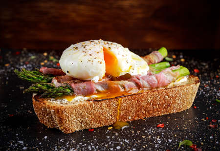 Grilled Toast witch Asparagus, Poached egg, bacon on stone background.