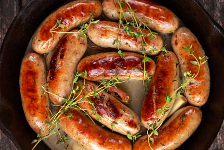 Home-made Pork Sausages in rustic pan with thyme.