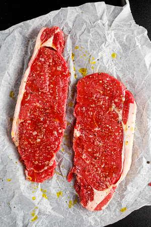 Raw seasoned sirloin prime british steaks on paper.