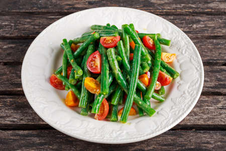 greenbeans: Green beans salad with Red, Yellow Tomatoes on white plate. Stock Photo