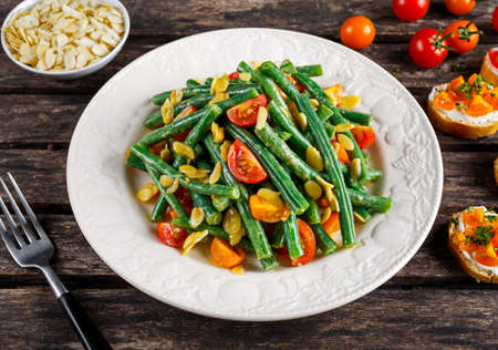 greenbeans: Green beans salad with Red, Yellow Tomatoes, bruschettas and flaked almond on white plate. Stock Photo