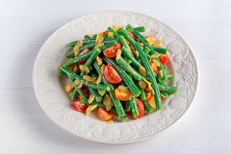 Green beans salad with Red, Yellow Tomatoes, bruschettas and flaked almond on white plate. Stock Photo