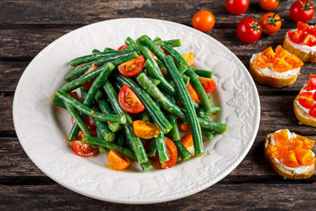 Green beans salad with Red, Yellow Tomatoes, bruschettas on white plate Stock Photo