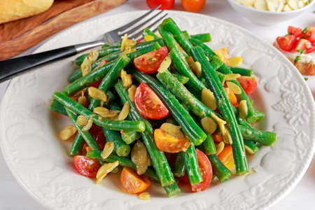 greenbeans: Green beans salad with Red, Yellow Tomatoes, bruschettas and flaked almond on white plate