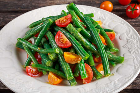 Green beans salad with Red, Yellow Tomatoes on white plate
