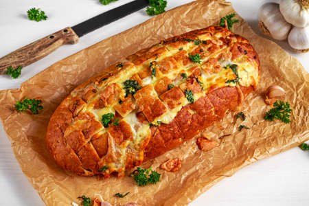 Homemade Cheese Garlic Pull Apart Bread with herbs on crumpled paper