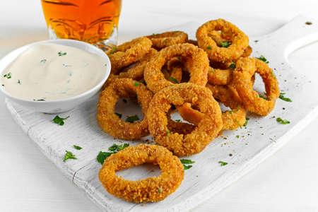 Fried Breaded Onion Rings con salsa y Light Beer en el tablero de madera blanco, fondo.