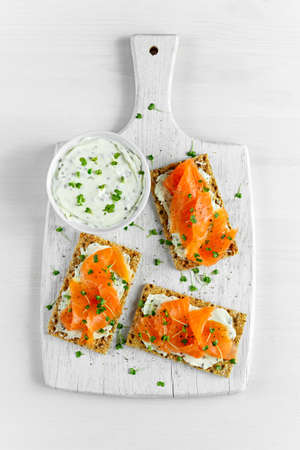 Homemade Crispbread toast with Smoked Salmon, Melted Cheese and cress salad. on white wooden board background. Stock Photo