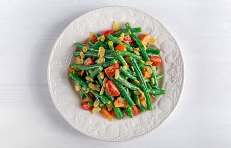 Green beans salad with bruschettas, Red, Yellow Tomatoes and flaked almond on white plate