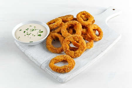 Fried Breaded Onion Rings with sauce. on white wooden board, background.