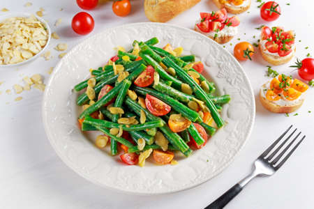 Green beans salad with Red, Yellow Tomatoes, bruschettas and flaked almond on white plate