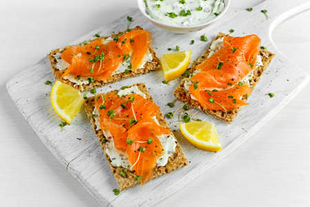 Homemade Crispbread toast with Smoked Salmon, Melted Cheese and cress salad. on white wooden board 스톡 콘텐츠