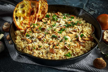 Mushroom Risotto in iron pan with herbs and parmesan cheese Foto de archivo