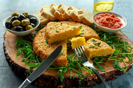 Spanish classic tortilla with potatoes, olives, tomatoes, rucola, bread and herbs.