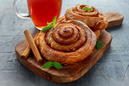 Freshly Baked Traditional Sweet Cinnamon Rolls, Swirl with hot black Tea and mint