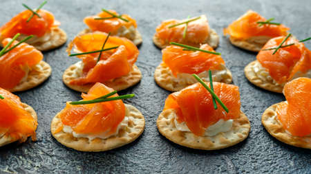 Smoked Salmon and soft chees canapes appetizers with chives on stone table. Stock Photo