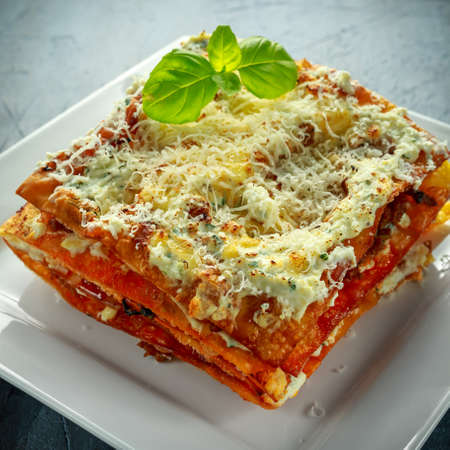 Homemade Crispy lasagna in iron pan with minced beef bolognese sauce, parmesan cheese and basil.