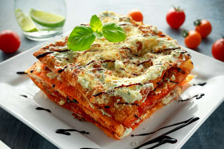 durum: Homemade Crispy lasagna in iron pan with minced beef bolognese sauce, parmesan cheese and basil