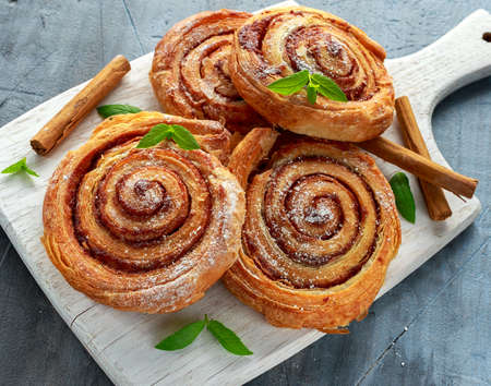 Freshly Baked Traditional Sweet Cinnamon Rolls, Swirl on white wooden board.