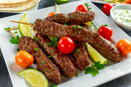 Homemade Kofta kebabs on skewers with pita, lime, vegetables, sweet chili and yogurt sauce on white plate. Stock Photo