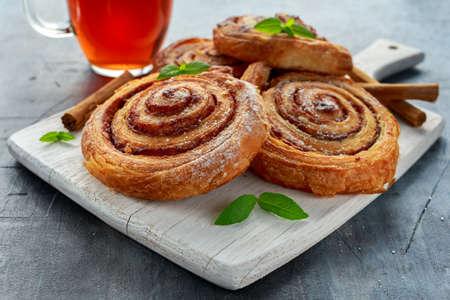 Versgebakken traditionele zoete kaneelbroodjes, swirl op wit houten bord met hete zwarte thee en munt